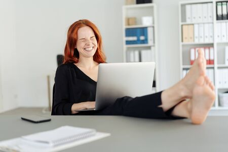 Carefree barefoot businesswoman laughing and giggling to herself at a joke on her laptop computer as she sits with her feet on the desk Banque d'images
