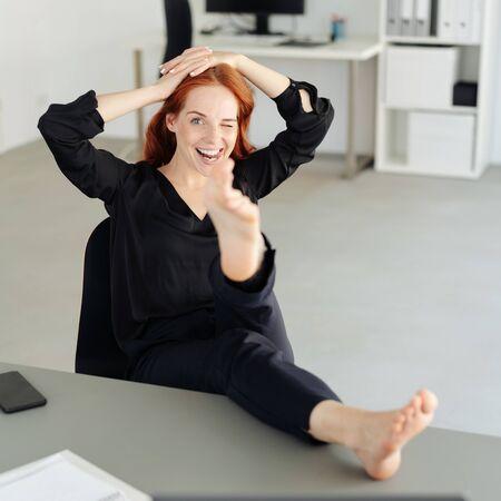 Verspielte entspannte junge Geschäftsfrau mit ihren Füßen auf dem Schreibtisch, die mit einem verschmitzten Lächeln in die Kamera zwinkert Standard-Bild