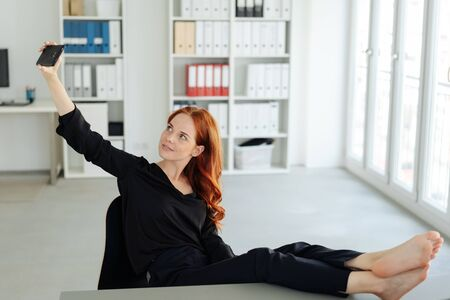 Jonge vrouw op blote voeten ontspannen met de voeten op het bureau terwijl ze selfie-foto's maakt met de mobiele telefoon voor het sociale netwerk op kantoor Stockfoto