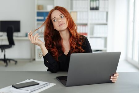 Thoughtful young businesswoman twiddling with her hair as she sits behind a computer at a desk in the office