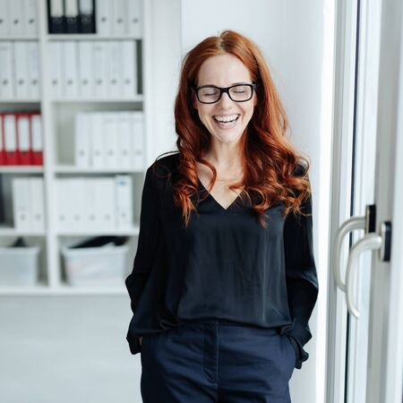 Attractive young businesswoman laughing at a joke as she stands with hands in pockets in the office