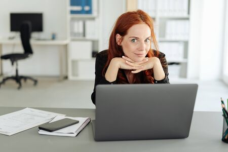 Young manageress giving a daring smile as she rests her chin on her hands behind her desk in the office as she formulates a new plan Stockfoto