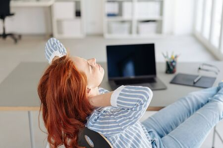 Businesswoman relaxing with feet on the desk and hands behind her neck as she sits back in her chair in the office