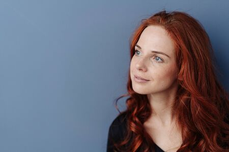 Thoughtful young redhead woman looking aside with a serious contemplative expression against a blue studio background with copy space Stock Photo
