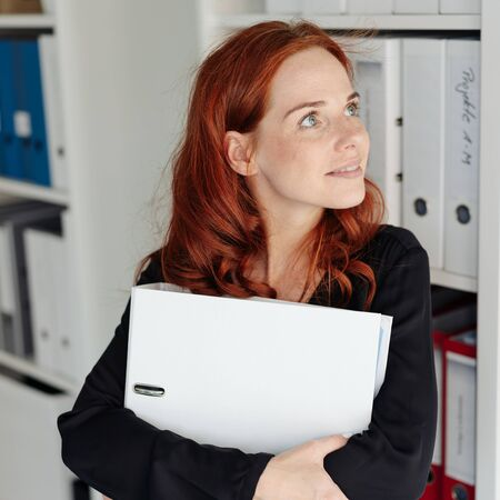 Portrait of a beautiful redhead woman and serene employee daydreaming while holding a white folder during work at the office