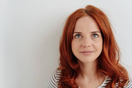 Close-up studio shot portrait of a beautiful and young redhead woman smiling while looking up as planning for the future against gray background for copy space
