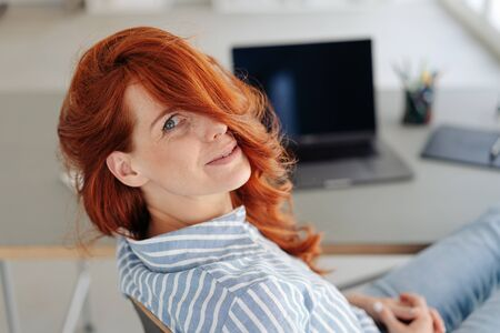 Fun young woman looking back over her shoulder with her long red hair flopping over her eyes as she relaxes at home Stockfoto