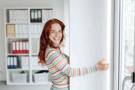 Cheerful young woman hugging a white column in the office as concept for professional stability and reliability