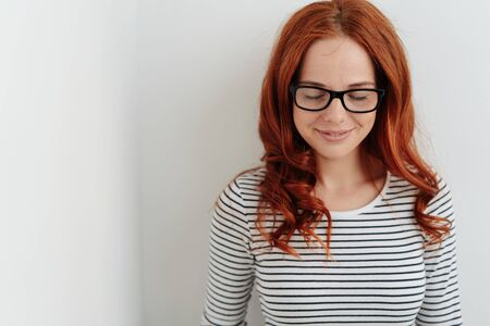 Young woman wearing glasses standing against a white wall smiling quietly to herself with downcast eyes and copy space 写真素材 - 129468457