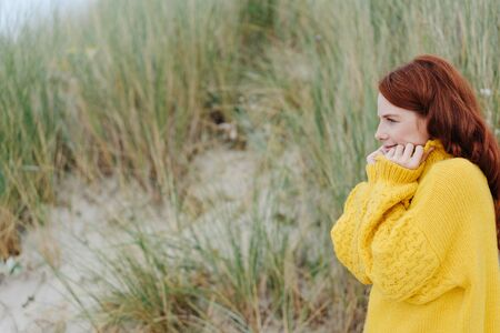 Cold young woman snuggling into a warm woolly yellow sweater as she stands on coastal sand dunes in autumn or winter with copy space