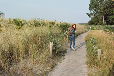 Young woman backpacking on a coastal boardwalk in the autumn sunshine looking back from a distance at the camera over her shoulder