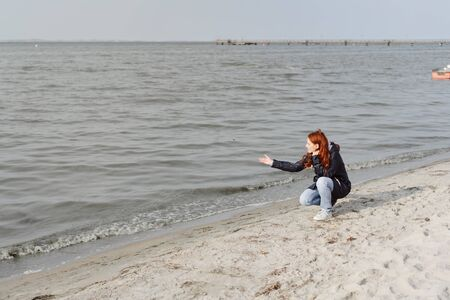 Young redhead woman on an autumn beach squatting on the sand at the edge of the surf gesturing at the ocean with copy space