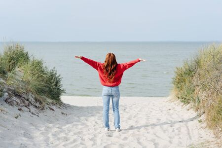 Young woman rejoicing at the warmth of the fall or autumn sun standing on a sandy footpath overlooking a tropical beach with outstretched arms