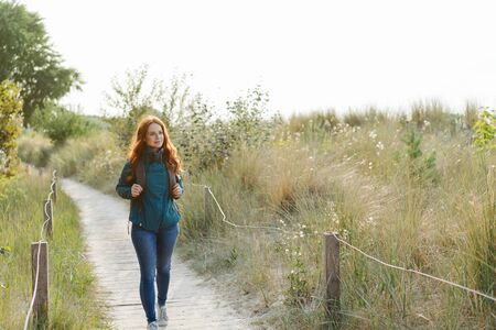 Fit healthy young woman hiking on a coastal boardwalk approaching the camera looking off to the side of scrub and bushes in an active outdoor lifestyle concept