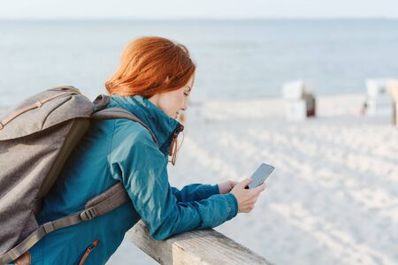 Young woman hiker relaxing at the beach in autumn standing leaning on a wooden parapet overlooking the sand reading a message on her mobile Stockfoto