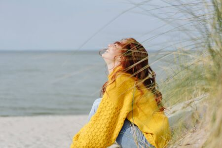 Happy young woman giggling to herself as she relaxes on sandy beach in autumn enjoying the warmth of the sun