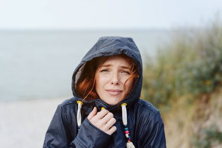 Freezing young woman snuggling into her anorak as she strolls outdoors on a cold autumn day on a beach looking anxiously at the camera