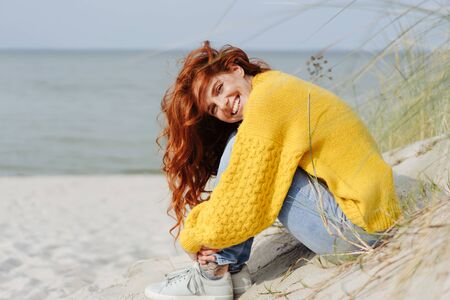 Smiling vivacious young woman relaxing on a tropical beach sitting on the sand dunes overlooking the sea enjoying the autumn sunshine Stockfoto