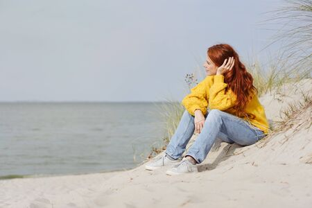 Pensive young woman sitting relaxing on a beach on a cold misty day in autumn enjoying the warmth of the sunshine as she stares out over the ocean