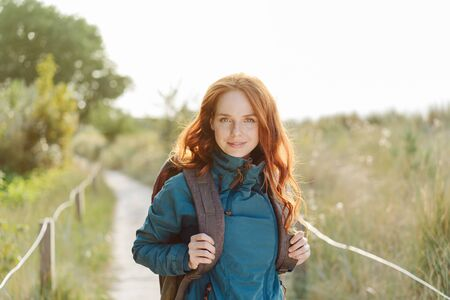 Intense young woman enjoying an autumn hike with her backpack standing on a coastal boardwalk staring intently at the camera backlit by the glow of the sun