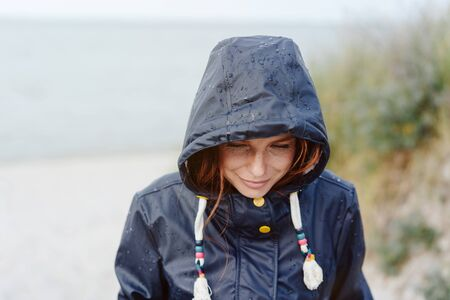 Thoughtful young woman smiling quietly to herself as she shelters from the cold weather under the hood of her anorak while walking on a beach in autumn