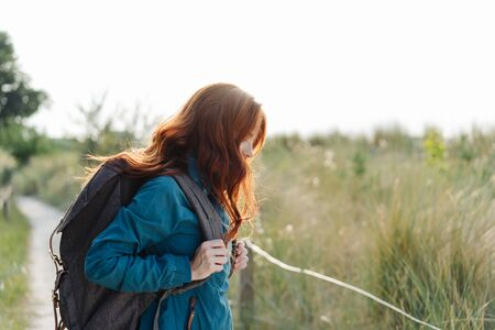 Young woman backpacker standing in profile on a wooden coastal boardwalk with her long red hair falling forwards covering her face