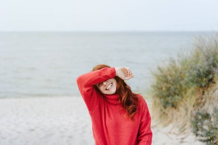 Happy young woman giggling to herself and covering her eyes with her arm in embarrassment as she walks on a cold sandy beach on a misty autumn day