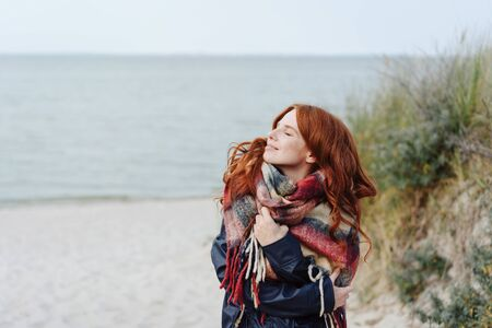 Active healthy young woman enjoying a sandy tropical winter beach standing in a warm anorak and scarf looking up into the sun with a blissful smile and closed eyes