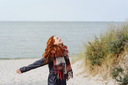 Joyful young woman in a warm winter scarf celebrating the cold weather as she enjoys a day outdoors on the beach in winter flinging back her arms with a happy smile Stockfoto