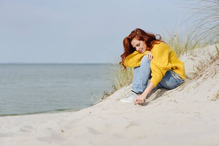 Thoughtful young woman drawing in beach sand with her finger as she relaxes on the dunes overlooking the ocean enjoying the autumn sunshine