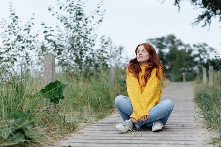 Young woman relaxing cross-legged on a coastal boardwalk with closed eyes and a blissful smile of contentment on a cold autumn day Stockfoto