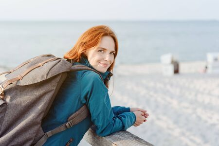 Smiling young woman backpacker at the seaside leaning on a wooden railing overlooking the beach and ocean looking back at the camera with a smile