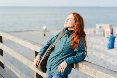 Blissful young woman enjoying the warmth of the autumn sun standing leaning on a wooden railing overlooking a sandy beach with closed eyes and a smile of contentment