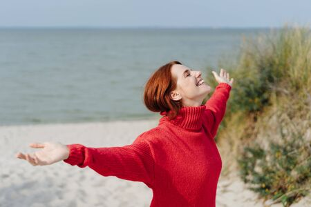 Happy joyful young woman with outstretched arms standing in a colorful red sweater on a sandy beach in autumn enjoying the sunshine Stockfoto