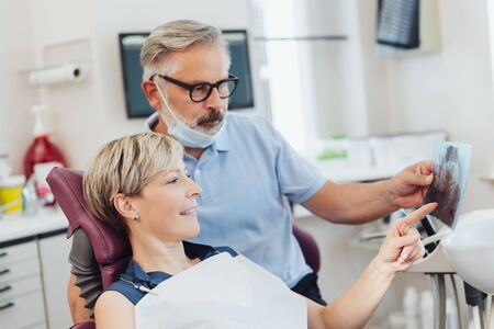 Dentist explaining an x-ray to a female patient during an examination in his surgery as she points out something on the film