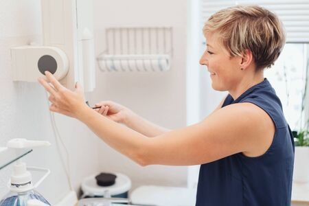 Smiling adult woman in blue vest using plain white dispenser attached to wall of completely white room