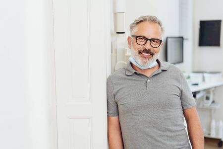 Relaxed dentist standing leaning against a surgery wall as he waits for the next patient looking at camera with a friendly smile 스톡 콘텐츠