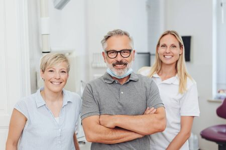 Smiling friendly dentist with his two happy female assistants or dental nurses posing together in his surgery