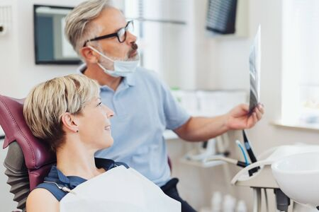 Dentist checking an X-ray with a female patient during a consultation in his surgery