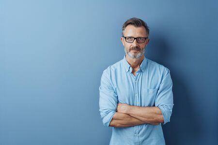 Hombre de mediana edad barbudo serio autoritario con los brazos cruzados de pie mirando fijamente a la cámara contra un fondo de estudio azul con espacio de copia
