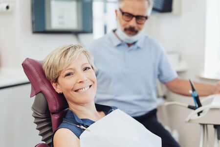 Smiling happy woman on the examination couch in a dental surgery turning to the camera with a beaming smile as he dentist looks on in the background