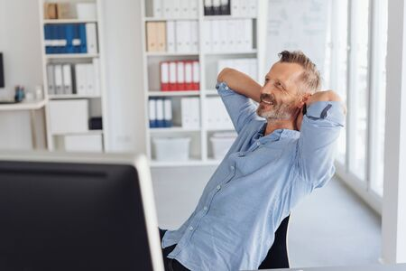 Relaxed happy businessman leaning back in his chair with his hands behind his back smiling with satisfaction as he looks up into the air in a high key office