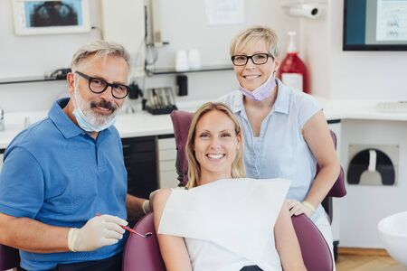 Smiling happy relaxed female patient at a dentist posing together in the surgery with the dental nurse during a consultation