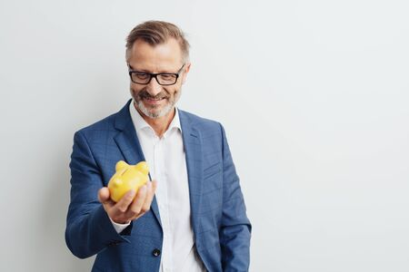 Successful businessman looking at his piggy bank held in his hand with a smile of satisfaction against a white background with copy space Stock Photo