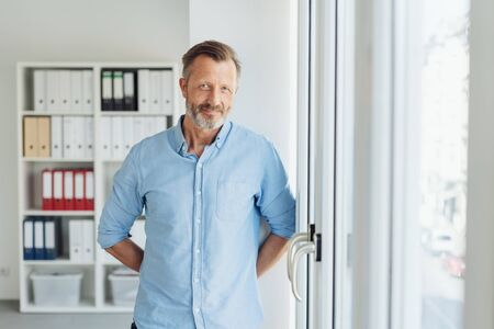 Relaxed smiling businessman in shirt sleeves standing with his hands behind his back alongside a glass door into the office in a high key portrait with copy space