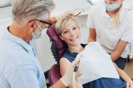 Dentisti che si preparano a lavorare sui denti di un paziente mentre la donna guarda la telecamera con un sorriso amichevole