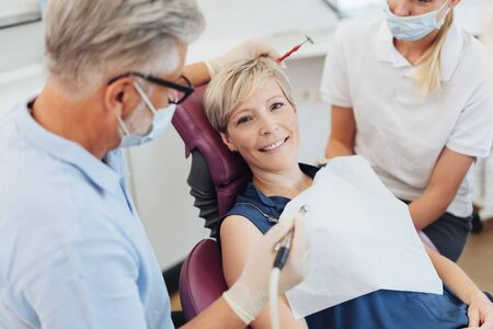 Dentists preparing to work on a patients teeth as the woman looks up at the camera with a friendly smile