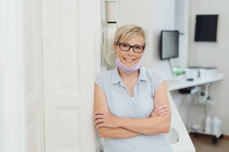 Smiling relaxed friendly female dentist or dental nurse leaning against a wall in the surgery with folded arms looking at camera