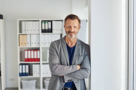 Confident relaxed businessman leaning against a white interior office wall with folded arms smiling at the camera