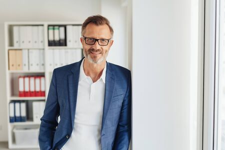 Smart bearded businessman wearing glasses leaning against a wall alongside glass exterior door in the office smiling at the camera Stock Photo